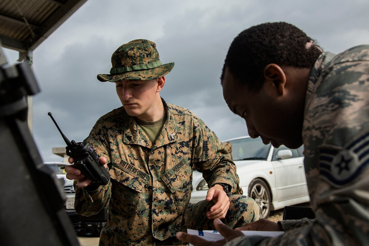 U.S. Marine Corps Cpl. Griffin Rutherford, an incident commander  with Chemical Biological Radiological Nuclear (CBRN) Platoon, G-3, 1st Marine Aircraft Wing (MAW), Marine Wing Headquarters Squadron 1, performs a radio check during a simulated CBRN response drill in Combat Town, Okinawa, Japan, March 21, 2016. Response drills allow CBRN Platoon to enhance the commander's capabilities by exercising the operability and efficiency of the consequence management set within the 1st MAW CBRN response element. (U.S. Marine Corps photo by MCIPAC Combat Camera Lance Cpl. Christian J. Robertson)